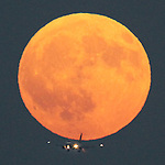 Airplane landing at SFO in the path of a September full moon rising.