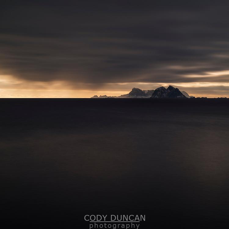 Mountain peaks of Værøy rise from sea, Å, Moskenesøy, Lofoten Islands, Norway