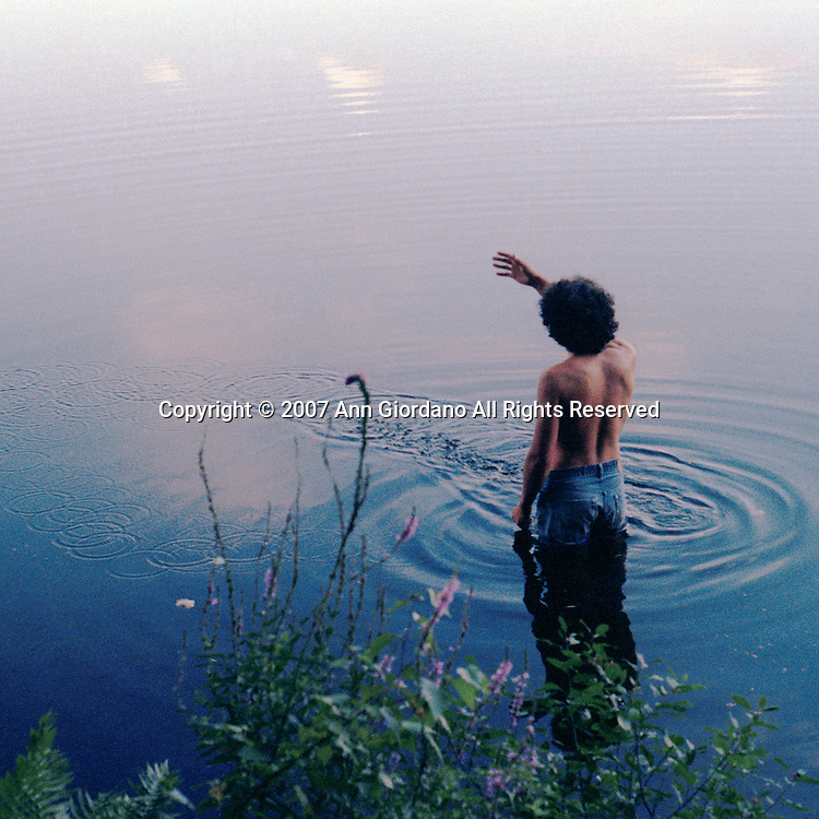 Rear view of shirtless young man standing in pond tossing a stone across water.