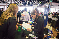 A job seeker, left, distributes her resume at the TechDay New York event on Thursday, April 23, 2015. Thousands attended to seek jobs with the startups and to network with their peers. TechDay bills itself as the world's largest startup event with over 300 exhibitors. (© Richard B. Levine)