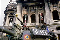 "ROMANIA, Pta. Palatului, today Pta. Revolutiei, Bucharest, 25.12.1989<br /> People rise against Ceausescu. The dictator has fled the city on dec. 22. At the central square intense figting with unidentifiable ""terrorists"" has been going on. Almost all buildings are damaged or partly destroyed. Army T-55 tanks at the burnt-out university library.<br /> © Andrei Pandele / EST&OST"
