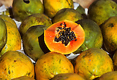 Brazil. Market stall display of Mamao (Papaya, Carica papaya) with fruit cut open to show the black seeds; medicinal plant.