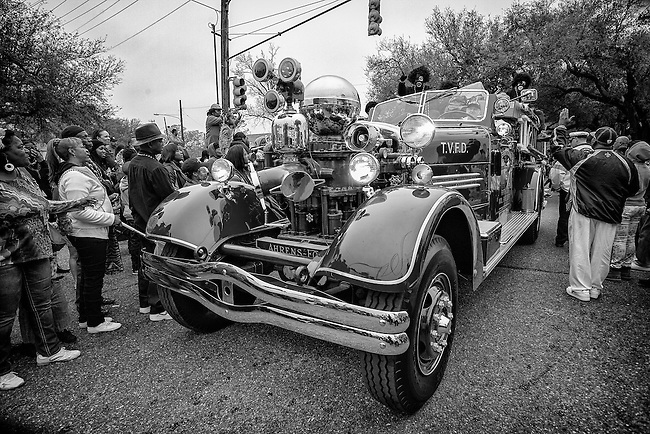 Members of the Zulu Social Aid & Pleasure Club ride on the Terrytown Fifth District Volunteer Fire Department's 1948 Ahrens-Fox Pumper in the 'Zulu Parade' on Jackson Avenue, the first parade on the morning of Mardi Gras Day on February 12, 2013 in New Orleans, Louisiana.