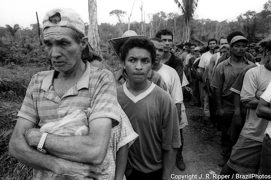 Contemporary slavery, Amazon rainforest, Tuerê Farm, State: Pará, Brazil. Wretched people lined up, waiting to be freed by The Special Group for the Repression of Forced Labour (Grupo Especial de Repressão ao Trabalho Forçado) or GERTRAF. It is made up of mobile groups that work in different regions of the country, investigating accusations of work conditions close to slavery on farms, charcoal works, plantations and sugar mills.  They are officials of the Ministry of Labour and they have support from the Federal Police.
