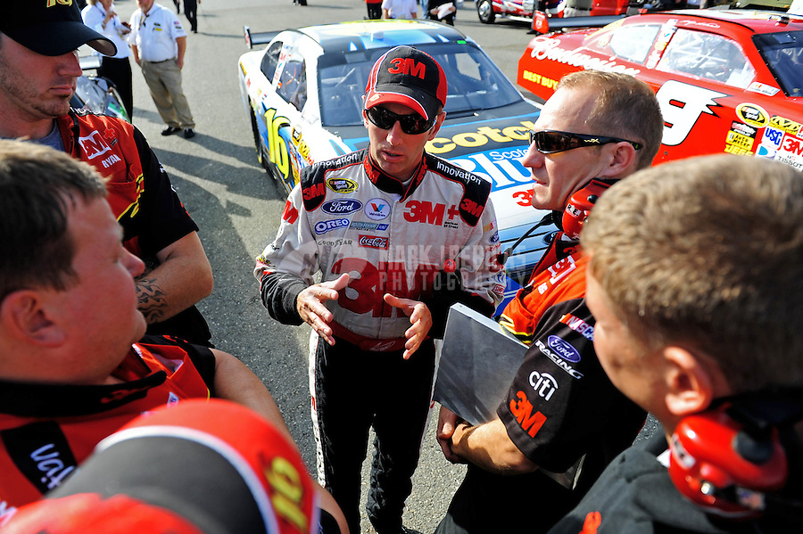 Oct. 9, 2009; Fontana, CA, USA; NASCAR Sprint Cup Series driver Greg Biffle (center) speaks with crew members during qualifying for the Pepsi 500 at Auto Club Speedway. Mandatory Credit: Mark J. Rebilas-