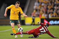 MELBOURNE, AUSTRALIA - OCTOBER 14: Brett Emerton from Australia evades a tackle by Hassan Madhafer from Oman in a AFC Asian Cup 2011 match between Australia and Oman at Etihad Stadium on October 14, 2009 in Melbourne, Australia. Photo Sydney Low www.syd-low.com