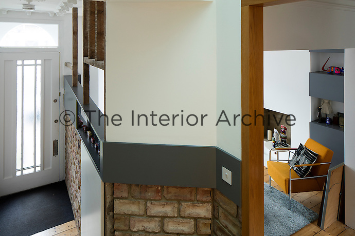 A Victorian home has been given a modernist aesthetic. For storage and display, a shelf begins at the front door and runs like ribbon throughout the house, providing visual continuity between its rooms. Leaving the original brickwork and timber framing exposed lends a rustic touch.