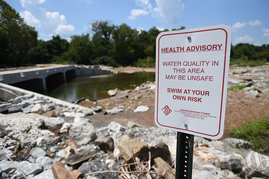 NWA Democrat-Gazette/J.T. WAMPLER A sign posted on the bank of the White River near the Dye Creek bridge in West Fork warns swimmers of poor water quality. The signs were posted in May after the Arkansas Health Department found a high level of E. coli bacteria in the water.