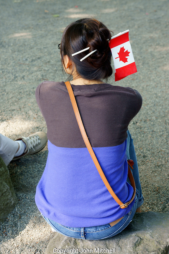 VANCOUVER, CANADA, 1st July 2013. Young woman of Asian descent with Canadian flags in her hair at Canada Day celebrations on Granville Island in Vancouver, BC. Canada Day or Fete du Canada is an annual national holiday celebrating Canada's birth as a nation  in 1867.