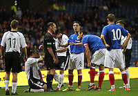 Referee Stevie O'Reilly restoring calm with Ian Black and Lee McCulloch as Ryan McGuffie sits on the ground in the Rangers v Queen of the South Quarter Final match in the Ramsdens Cup played at Ibrox Stadium, Glasgow on 18.9.12.