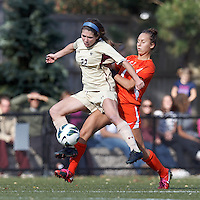 Boston College defender McKenzie Meehan (22) attempts to control the ball as University of Miami defender Allie Rossi (4) defends..After two overtime periods, Boston College (gold) tied University of Miami (orange), 0-0, at Newton Campus Field, October 21, 2012.