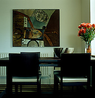 A stainless steel bowl beside a vibrant flower arrangement on the dining table echoes the metalic sheen in the abstract painting on the adjacent wall