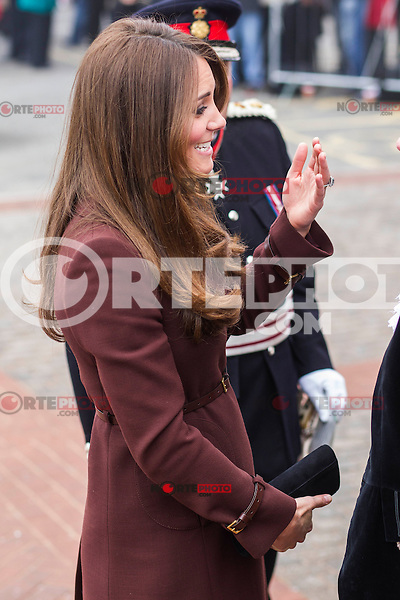 PAP0313KG451.Crowds of well-wishers waving Union Jack flags lined Grimsby's streets to catch a glimpse of the Duchess of Cambridge. She beamed as she was presented with colourful bouquets of flowers and a teddy bear.