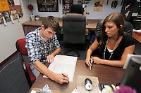 Brandon Tanner, left, of Vienna, Ill., fills out paperwork to transfer to Southern Illinois University, while Sarita Robinson, Director of SIU Service Center - Shawnee Community College, right, guides him through the process in the SIU Service Center located within Shawnee Community College in Ullin, Ill., on Wednesday, July 13, 2011. Seven SIU Service Centers such as this one have partnered with Illinois state community colleges in a pilot program where students in the program will apply and be accepted at the four-year institution, but complete their first two years at the community college.