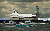 The space shuttle Enterprise, atop a barge,  passes the Statue of Liberty in New York on its way to the Intrepid Sea, Air and Space Museum where it will be permanently displayed, Wednesday, June 6, 2012. .Mandatory Credit: Bill Ingalls / NASA via CNP