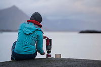 Female hiker cooks with stove near coast, Lofoten Islands, Norway
