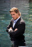 Young man wearing business suit standing in water