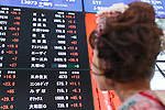 A woman wearing traditional Japanese kimono looks at an electronic stock board displaying the first session of the year at the Tokyo Stock Exchange (TSE) on January 4, 2017, Tokyo Japan. The Nikkei Stock Index opened at 19,298.68, higher than the last trading day of 2016. (Photo by Rodrigo Reyes Marin/AFLO)