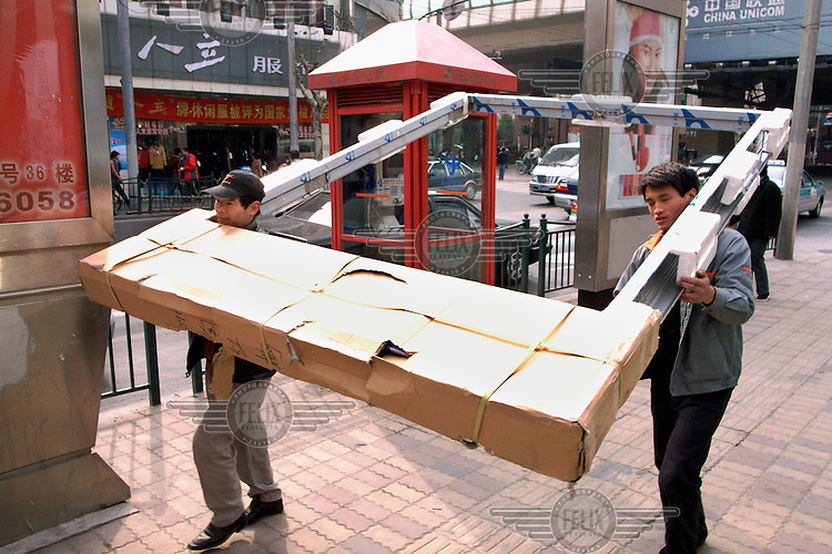 Workers carry a large door frame on a street.