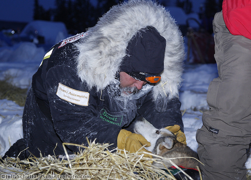 Friday March 9, 2012    Musher Scott Jansen cuddles with one of his dogs in the early morning at the half-way checkpoint at Cripple.   Iditarod 2012.