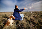 In Washington's sage country, a research biologist keeps company with his Brittany spaniel for long hours as he uses radio telemetry to locate and track the endangered Greater sage grouse.