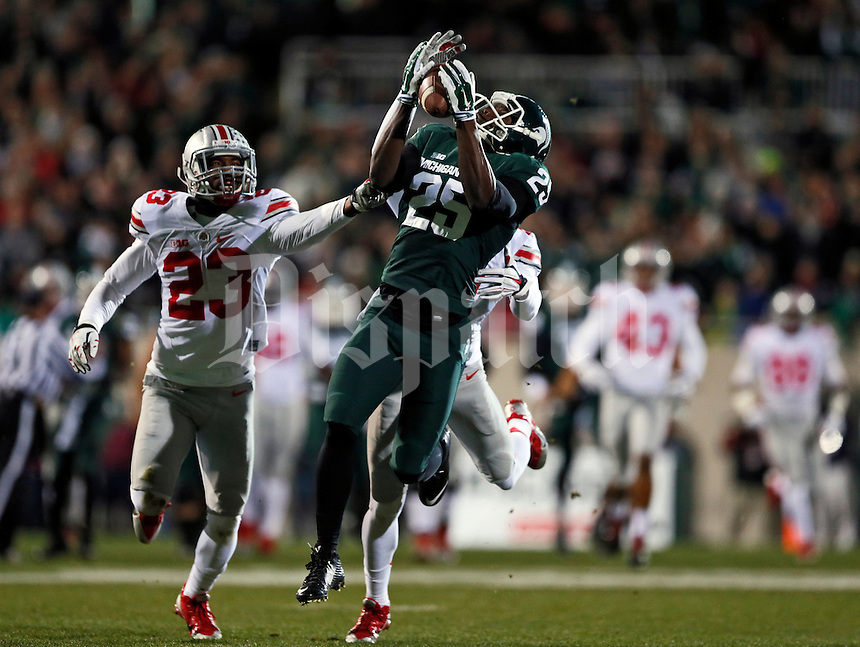 Michigan State Spartans wide receiver Keith Mumphery (25) catches a pass behind Ohio State Buckeyes safety Tyvis Powell (23) during the first quarter of the NCAA football game at Spartan Stadium in East Lansing, Michigan on Nov. 8, 2014. (Adam Cairns / The Columbus Dispatch)