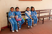 Arequipa, Peru. A. Antoniano (public elementary and secondary school). Portrait of four students (girls, elementary-school aged, Peruvian).on a bench in breezeway at their school. No MR. ID: AL-peru.