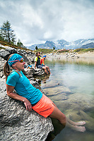 Runners relaxing and cooling off their feet at a small lake above Zermatt, while running the Via Valais, a multi-day trail running tour connecting Verbier with Zermatt, Switzerland.