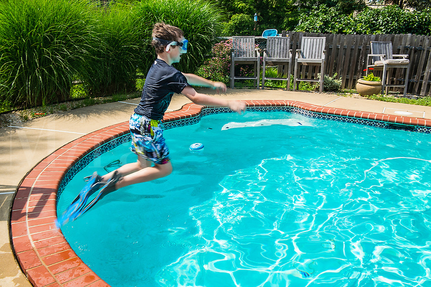 Boy jumping into a pool with flippers and goggles.