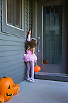 USA, Illinois, Metamora, Girl (6-7) in Halloween costume knocking to doors