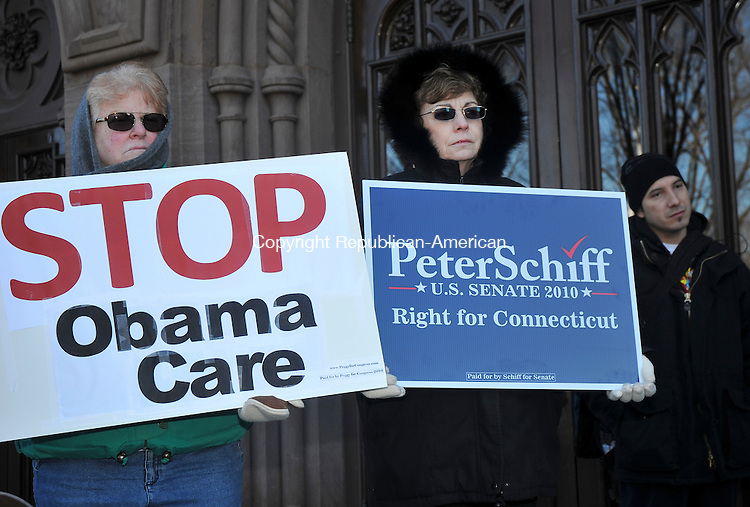 NEW HAVEN, CT-16 JANUARY 2010-011610IP04- Marie-Anne Barnhart, left, and Joan Bennett, both of New Haven and members of the Tea Party movement, hold political signs, as Peter Schiff, a financial expert and author who is running for the Republican nomination for U.S. Senate, speaks during a rally against &quot;Obamacare&quot; on Church St. in New Haven on Saturday. <br /> Irena Pastorello Republican-American