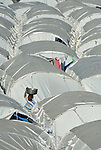 "A woman walks through a ""tent city"" for homeless families set up in the Belair neighborhood of Port-au-Prince, Haiti, in the wake of a devastating earthquake that shook the Caribbean island nation on January 12."