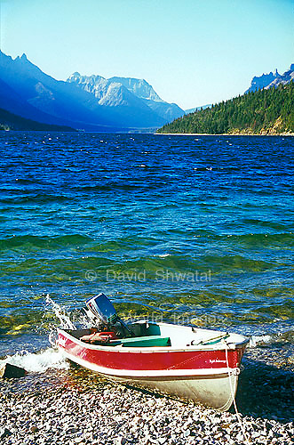 A speed boat on the pebble beach shore of Cameron Bay in Upper Waterton Lake water sky and mountains Alberta Canada