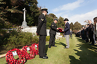 A representative from the St Andrew's  Association collects a wreath of poppies to lay at the Cross of Sacrifice during the Remembrance Sunday ceremony at the Hodogaya, Commonwealth War Graves Cemetery in Hodogaya, Yokohama, Kanagawa, Japan. Sunday November 11th 2018. The Hodagaya Cemetery holds the remains of more than 1500 servicemen and women, from the Commonwealth but also from Holland and the United States, who died as prisoners of war or during the Allied occupation of Japan. Each year officials from the British and Commonwealth embassies, the British Legion and the British Chamber of Commerce honour the dead at a ceremony in this beautiful cemetery. The year 2018 marks the centenary of the end of the First World War in 1918.