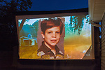 "Merrick, New York, USA. 11th June 2017.  Picture of young boy shown on large screen is ""American Grit"" TV show contestant CHRIS EDOM, now 48 of Merrick, during Season 2 premiere of the reality show. Edom family and neighbors watched Episode 1 of the Fox network reality TV show on large screen in their backyard. Edom was the last contestants picked for a team."