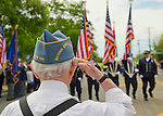 Merrick, New York, U.S. - May 26, 2014 - A veteran salutes fire fighters marching in The Merrick Memorial Day Parade and Ceremony, hosted by American Legion Post 1282 of Merrick, honors those who died in war while serving in the United States military.