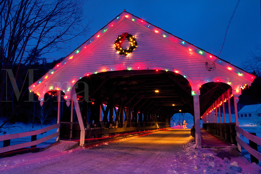 Covered bridge at Christmastime decorated with Christmas lights.