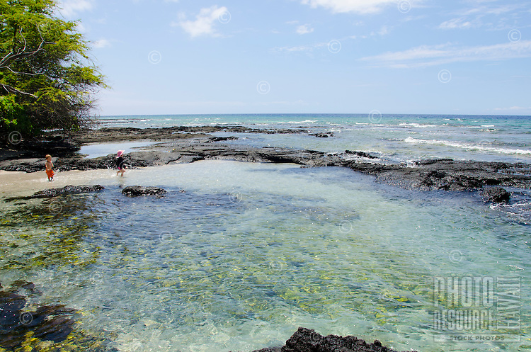 Two local kids play in a shallow tide pool at a beach in Puako, South Kohala, Big Island.