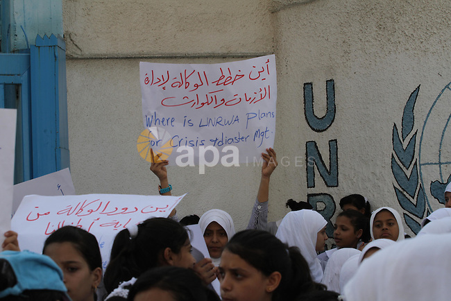 Palestinian Students hold banners during a protest to get out displaced from their schools in front of the headquarters of UNRWA in Gaza City September 18, 2014. An open-ended ceasefire between Israel and Hamas-led Gaza militants, mediated by Egypt, took effect on August 26 after a seven-week conflict. It called for an indefinite halt to hostilities, the immediate opening of Gaza's blockaded crossings with Israel and Egypt, and a widening of the territory's fishing zone in the Mediterranean. Photo by Mohammed Asad