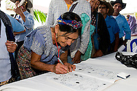 A Mayan woman adds her signature to the redeclaration of the communities of Huehuetenango as being 'Free of Mines'. <br /> The event was part of the celebrations of the third anniversary of the declaration. Organised by the ADH (The Assembly for the Defence of the Territory).<br /> Jacaltenango, Guatemala 2011.