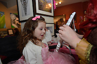 Amelia Cruz, three, the daughter of Catherine Thomason, reacts to her make-up applied by professional face and body artist Cat Cabajar at the Princess make-up party held at The Painted Cat.