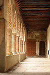 Looking down a corridor with wooden beams, painted columns, and 15th century frescos above two wooden doors at the end in the S. Maria delle Grazie Chiostro, or convent, in Gravedona, a town on Lake Como, Italy.