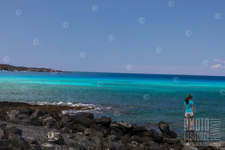 An Asian woman walks on the rocky seashore at Kiholo Bay, Big Island.