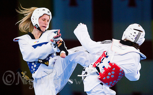 05 MAY 2012 - MANCHESTER, GBR - Edina Kotsis (HUN) of Hungary (left) tries to block a kick from Floriane Liborio (FRA) of France during the women's -57kg category final at the 2012 European Taekwondo Championships at Sportcity in Manchester, Great Britain .(PHOTO (C) 2012 NIGEL FARROW)