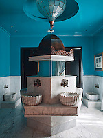 This guest bathroom features a central marble fountain with six separate wash areas and two ablution areas. The copper top to the fountain was inspired by Ottoman design and produced by Hall, who also designed the glass and copper chandelier. The walls and ceiling are painted in high gloss turquoise lacquer