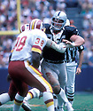 Los Angeles Raiders Howie Long (75) in action during a game against the Washington Redskins on September 14, 1986 at Robert F. Kennedy Memorial Stadium in Washington, D.C.. The Redskins beat the Raiders 34-14. Howie Long was inducted to the Pro Football Hall of Fame in 2000.