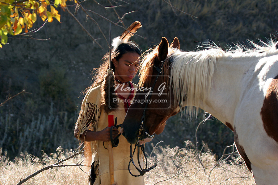 A Native American Indian boy wearing a feather standing next to a horse holding a spear with buffalo hide on it