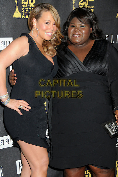 "MARIAH CAREY & GABOUREY ""GABBY"" SIDIBE .25th Annual Film Independent Spirit Awards - Press Room held at the Nokia Event Deck at L.A. Live, Los Angeles, California, USA, 5th March 2010..indie half length black dress hand on hip smiling sleeveless bracelets hoop earrings .CAP/ADM/BP.©Byron Purvis/AdMedia/Capital Pictures."