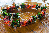 A beautiful cigar lei rests on a mango wood table, Hawai'i.