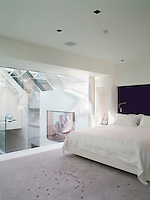 Purple spots on the Paola Lenti rug in the bedroom add a dash of subtle colour to the grey, echoing the purple headboard